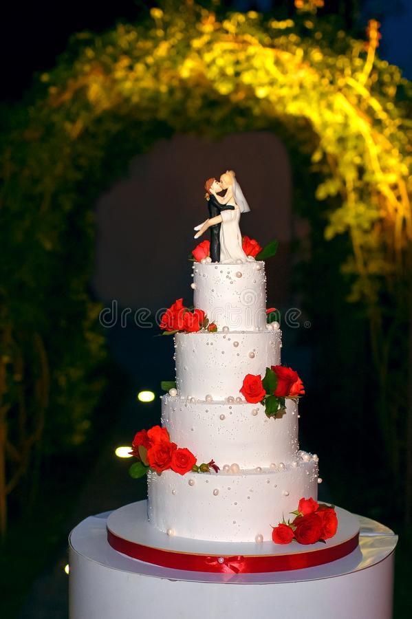 Funny figurines suite at a luxury wedding white cake decorated with fresh flowers royalty free stock photos