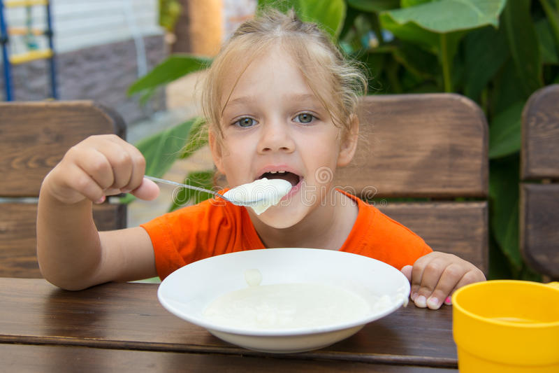 Funny five-year girl with pleasure eats porridge for breakfast stock photography
