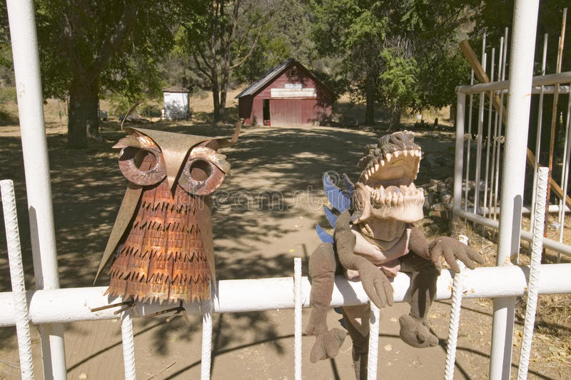 Funny folk art of owl and dinosaur sitting on fence. royalty free stock images