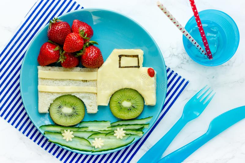 Funny food idea for kids - cheese sandwich with strawberry. And kiwi shaped car on a plate top view stock image