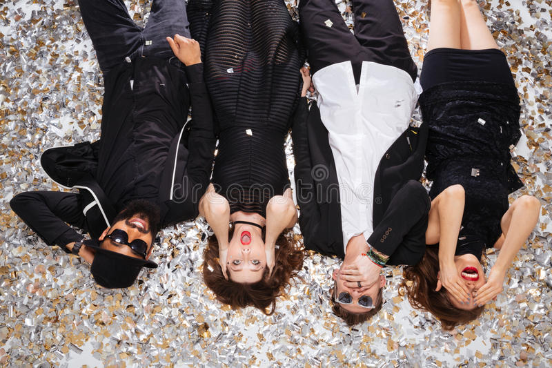 Funny friends grimacing and lying on sparkling confetti royalty free stock images