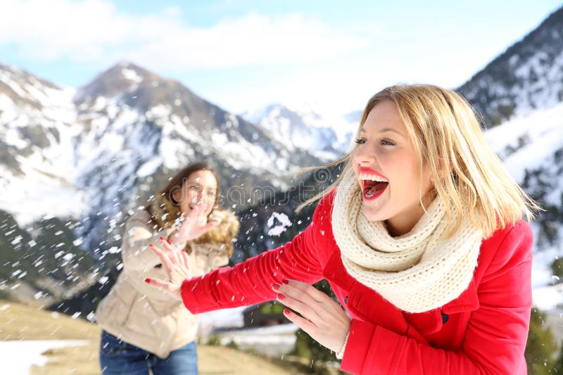 Funny friends joking throwing snowballs. Two funny friends joking throwing snowballs in the mountain on winter holiday stock photo