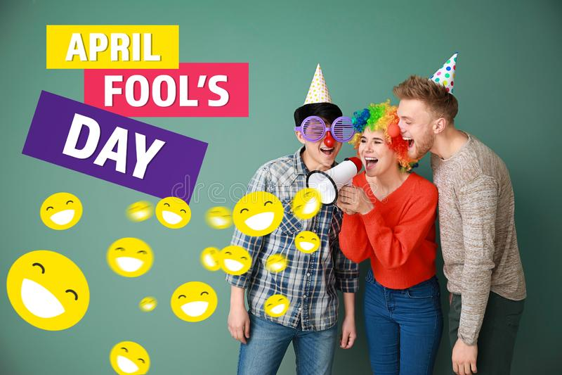 Funny friends with megaphone on color background. April Fools' Day prank royalty free stock image