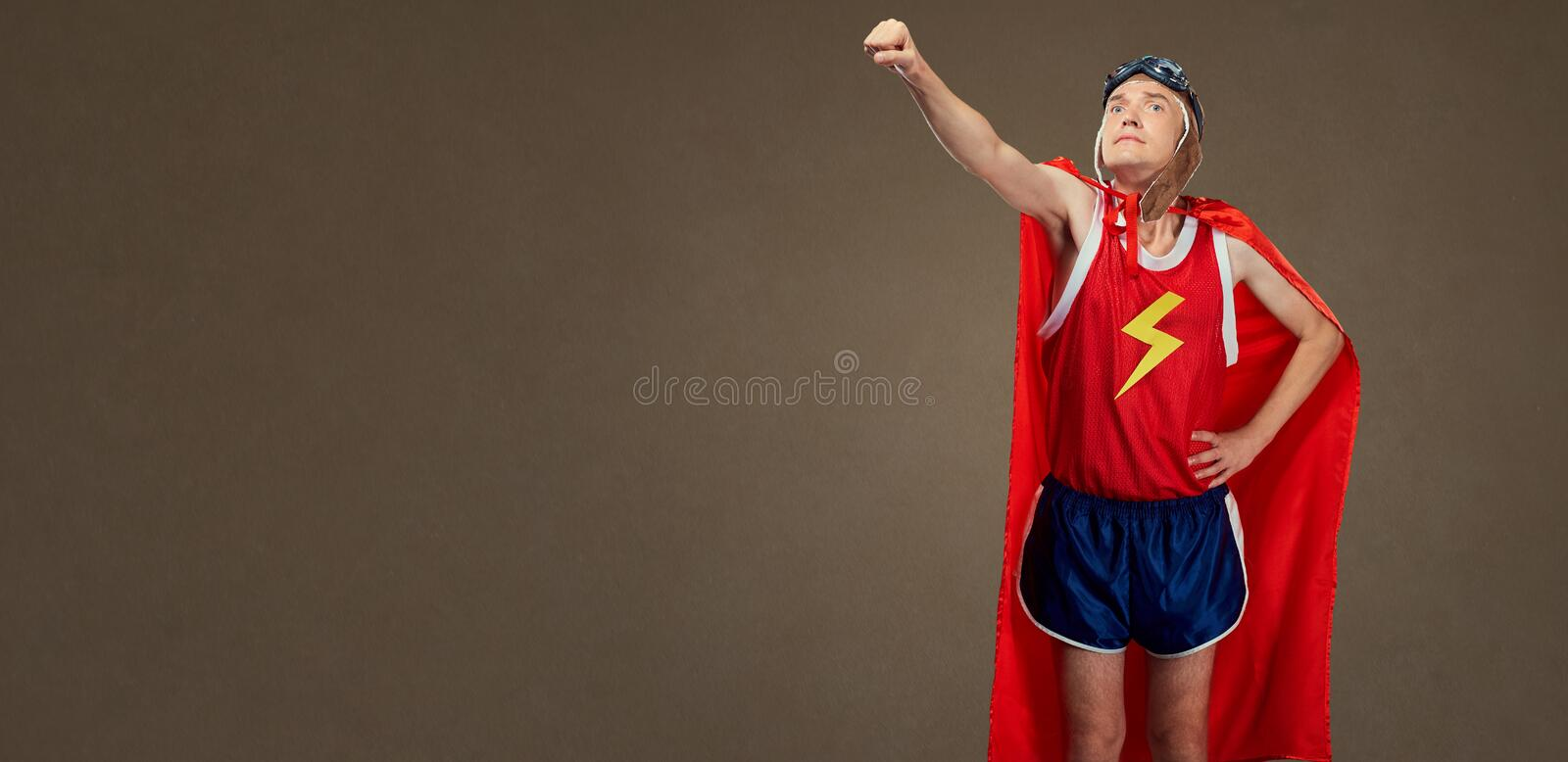 Funny funny cheerful man in a superhero costume in sports clothe. S. Humor in sport royalty free stock image