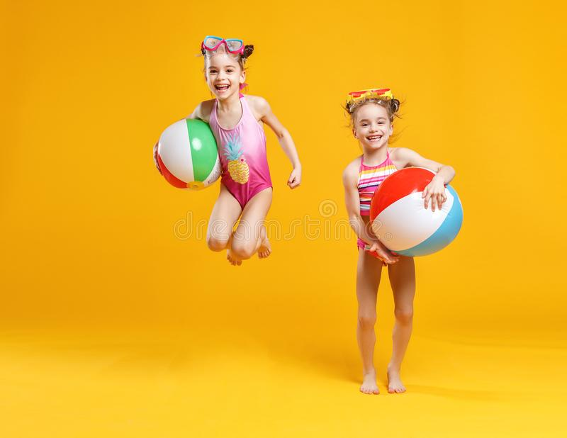Funny funny happy children in bathing suits jumping on colored stock photos