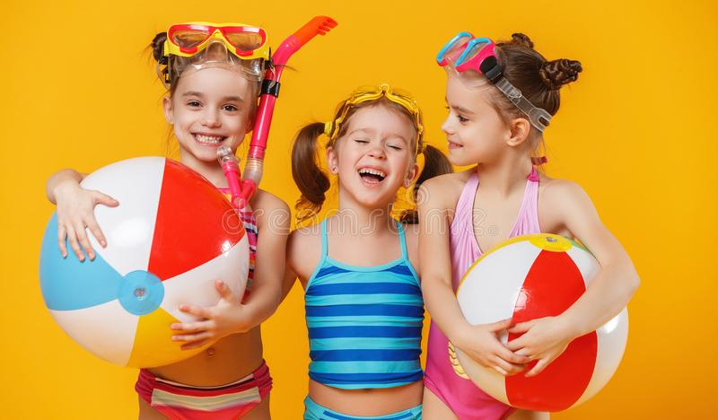 Funny funny happy children in bathing suits jumping on colored stock photo