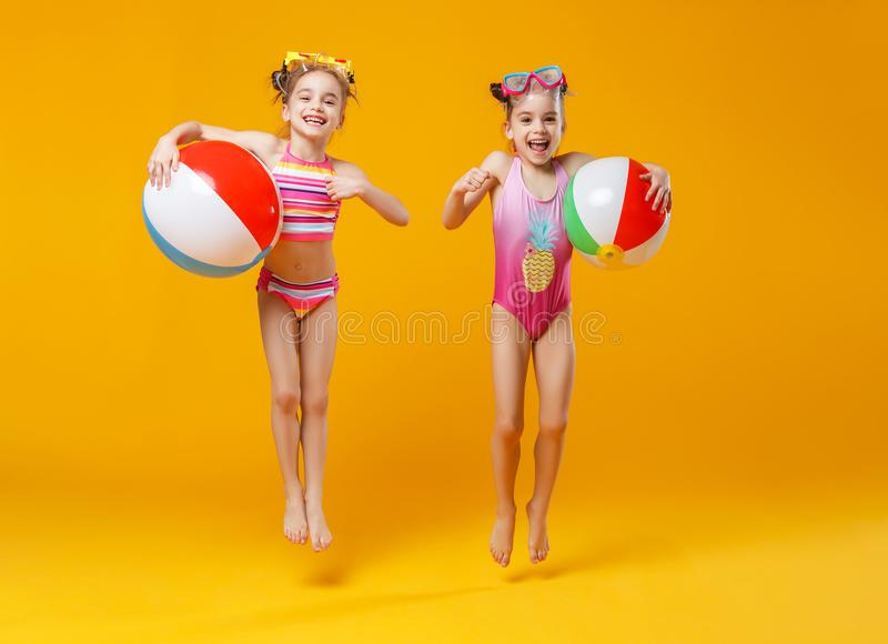 Funny funny happy children in bathing suits jumping on colored royalty free stock image
