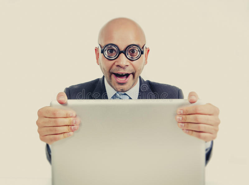 Funny geek and freak bald head businessman with computer laptop wearing thick glasses looking nerd stock photography