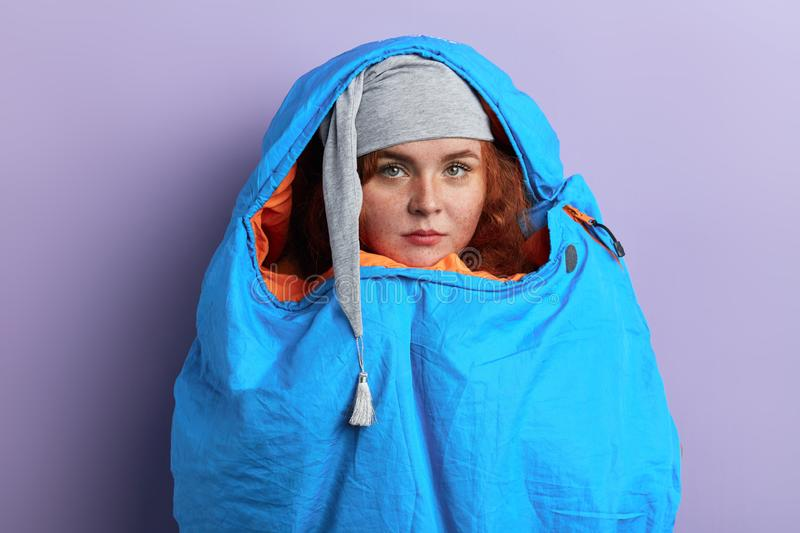 Funny ginger hiker hiding into the blue sleeping bag. Close up portrait, isolated blue background, fear concept, morning stock photography