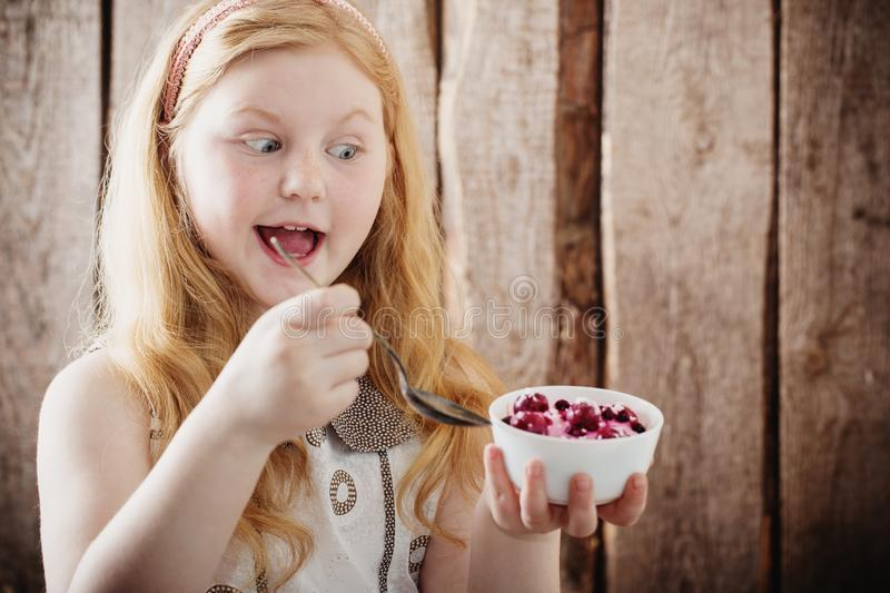 Funny girl with berries in plate royalty free stock image