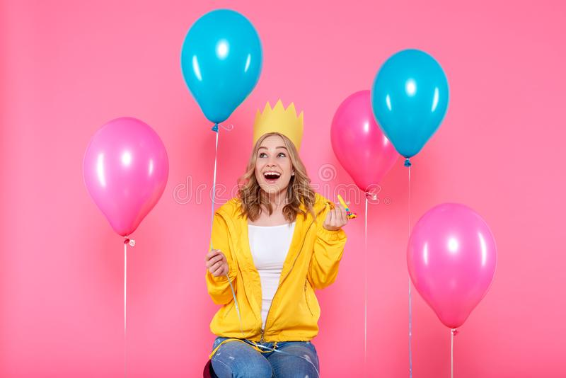 Girl in birthday hat, balloons and blowout horn on pastel pink background. Attractive trendy teenager celebrating birthday. Funny girl in birthday hat, balloons royalty free stock photography