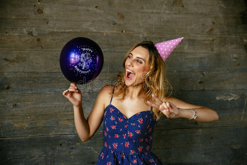 Funny girl in birthday hat celebrating birthday. Cheerful attractive girl having fun while celebrating birthday, showing peace gesture, looking at balloon royalty free stock images