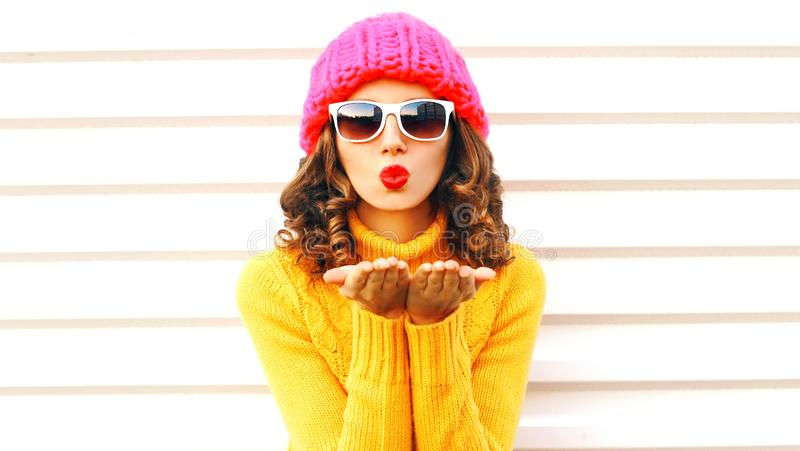 Funny girl blowing red lips makes sends air kiss wearing colorful knitted ha stock image