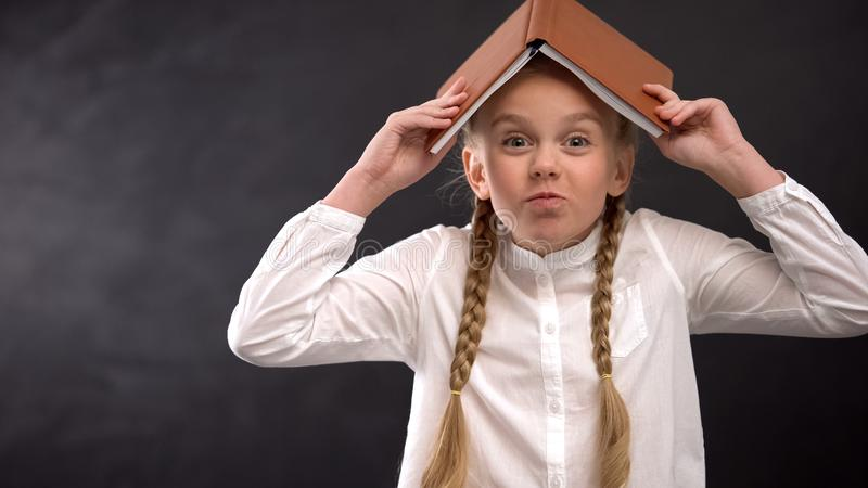 Funny girl with book on head fooling around against blackboard, school life. Stock photo royalty free stock image