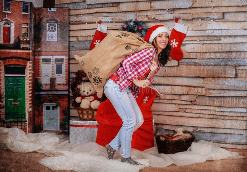 Funny girl carrying a bag of gifts. The concept of the New Year stock images