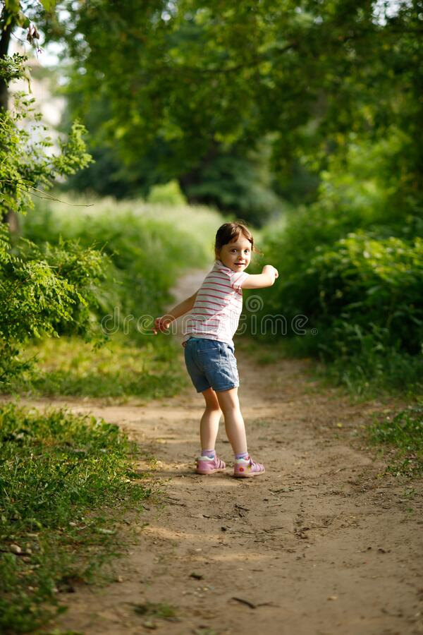 Free Funny Girl Child In A White Striped T-shirt And Blue Shorts Looks Back And Runs Away. Catch-up Game Stock Images - 175750374