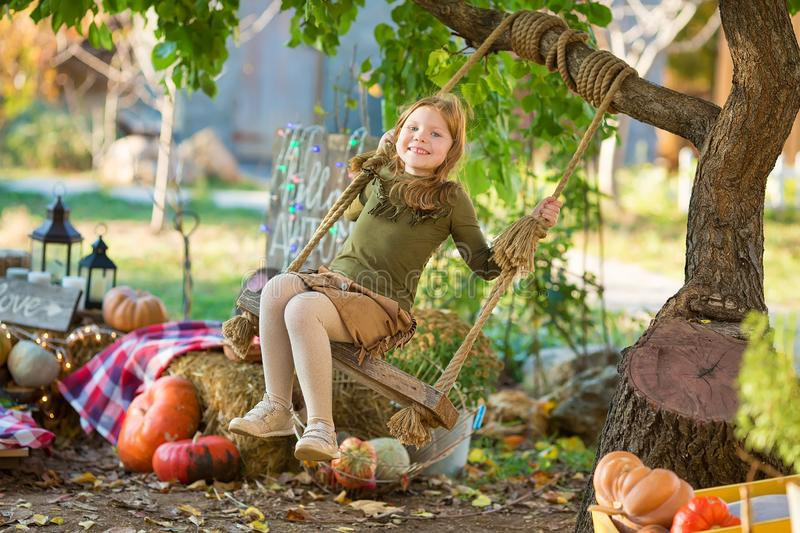 Funny girl in halloween green costume playing outdoor with spooky jack pumpkins with scary faces sitting on swing west royalty free stock images