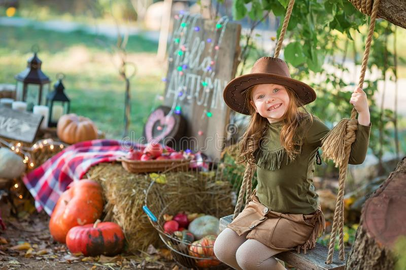 Funny girl child kid in halloween green costume playing outdoor with spooky jack pumpkins with scary faces sitting on swing west stock photography