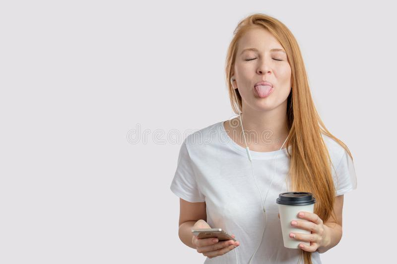 Funny girl with closed eyea and protruded tongue is coming into notice. Lovely emotional hipster is showing apathy towards the problem. facial gesture concept royalty free stock photos