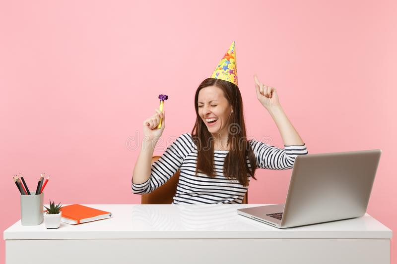 Funny girl with closed eyes in birthday party hat with playing pipe dancing enjoy celebrating while sit work at desk. With laptop isolated on pink background stock photos