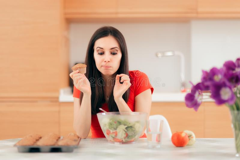 Woman Eating a Cupcake instead of Apples or Salad royalty free stock photography