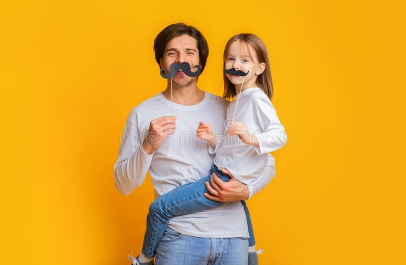 Funny girl and dad have mustaches on sticks stock photo