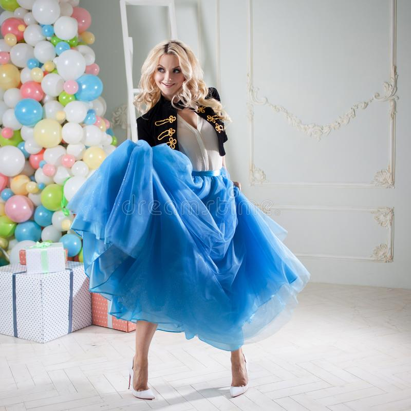 Funny girl dancing in blue skirt. Beautiful young woman blonde in a fabulous interior. royalty free stock images