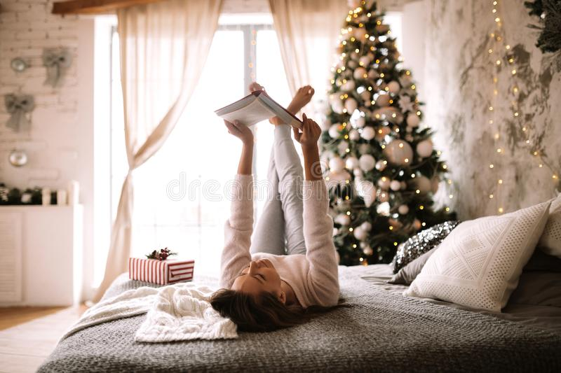 Funny girl dressed in white sweater and pants reads a book liying on the bed with gray blanket, white pillows and a New royalty free stock photo