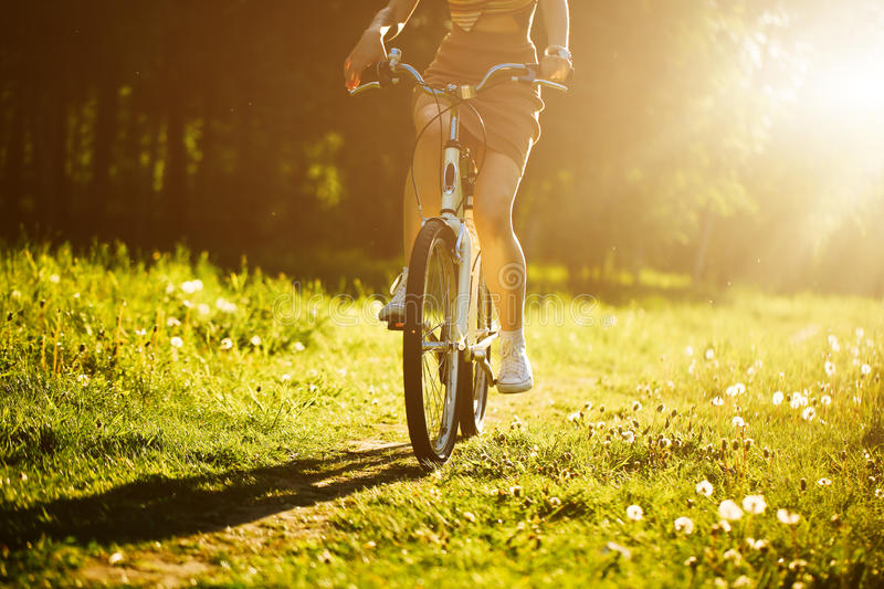 Funny girl driving bicycle outdoor. Sunny summer lifestyle concept. Woman in dress and hat in Field with dandelions. Female ride in park. Light photo effect royalty free stock photos