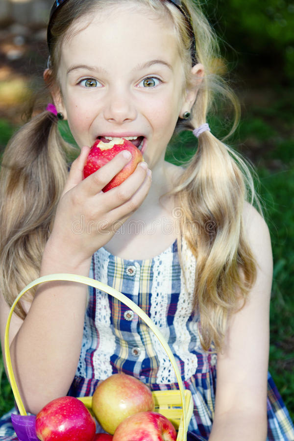 Funny girl eating apple royalty free stock photo