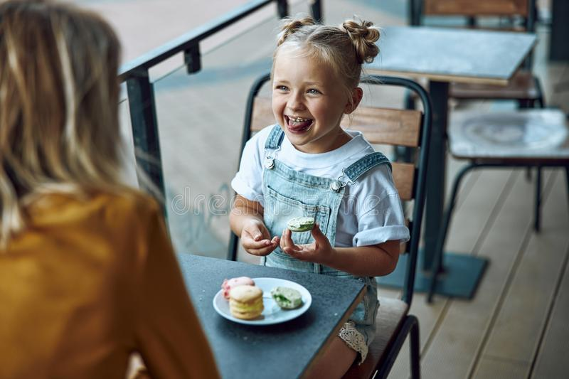 Funny girl eating cookie and smiling stock photo royalty free stock photo
