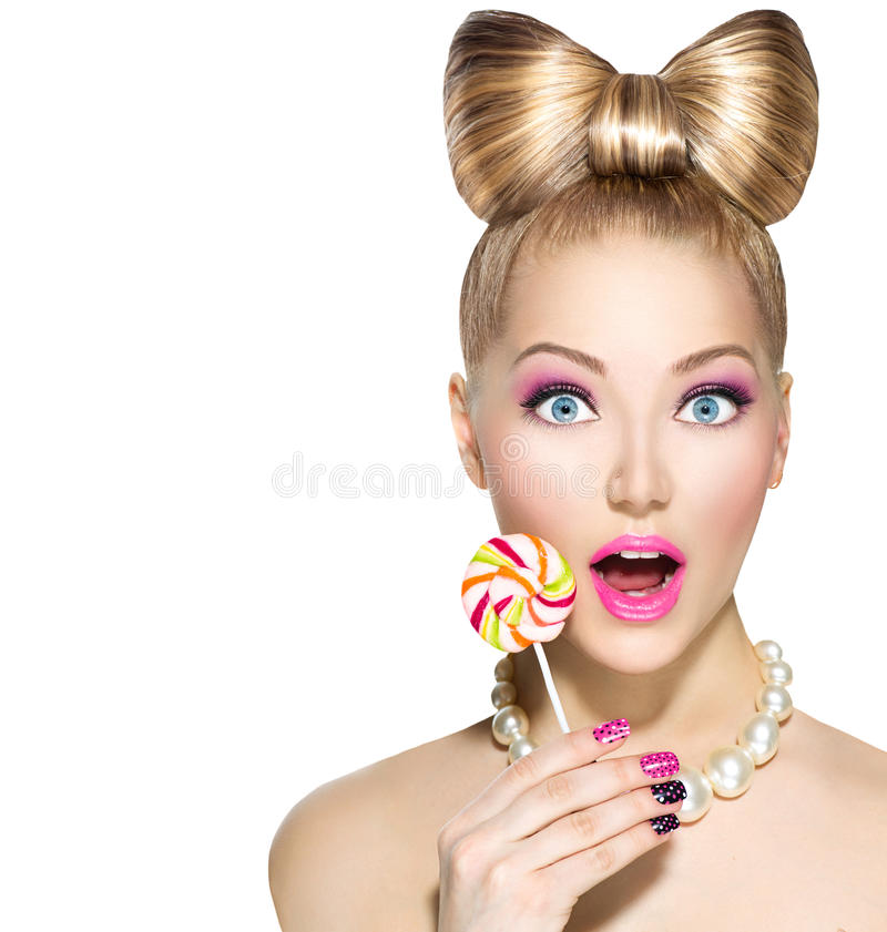 Funny girl eating lollipop. Funny girl with bow hairstyle eating colorful lollipop stock image