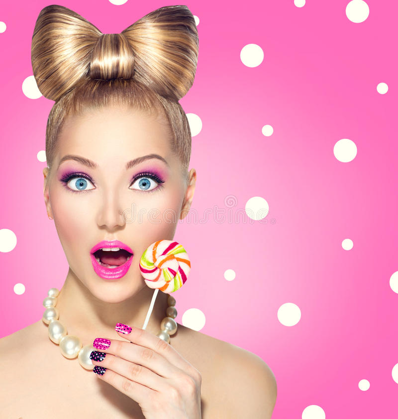 Funny girl eating lollipop. Over pink polka dots background royalty free stock photos