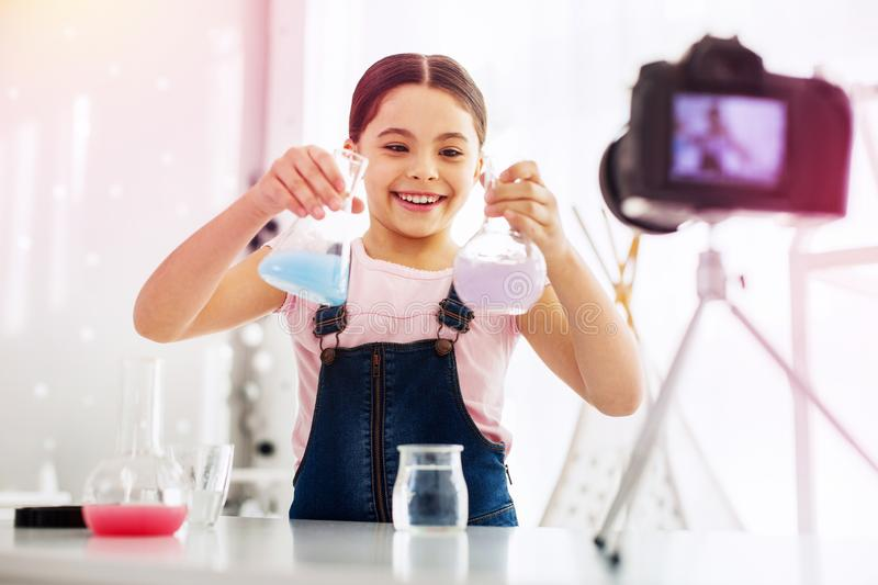 Funny girl fond of chemistry filming video while making experiment stock photography