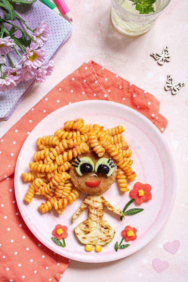 Funny Girl Food Face. With Cutlet, Pasta and Vegetables royalty free stock photography