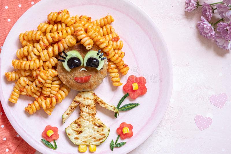 Funny Girl Food Face. With Cutlet, Pasta and Vegetables stock photo