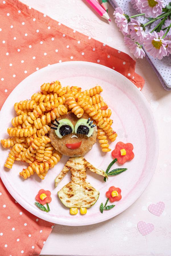 Funny Girl Food Face. With Cutlet, Pasta and Vegetables stock photos