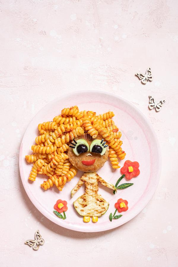Funny Girl Food Face. With Cutlet, Pasta and Vegetables stock photography