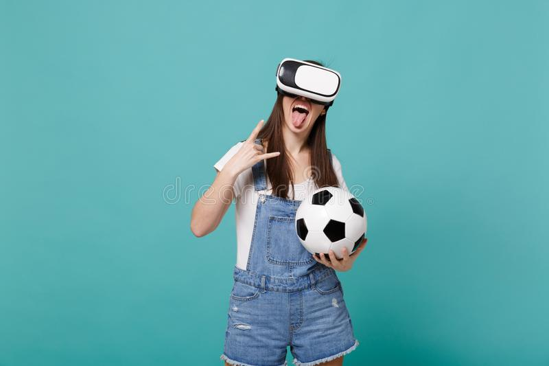 Funny girl football fan in headset hold soccer ball showing tongue, horns up gesture isolated on blue turquoise. Background. People emotions, sport family stock photos