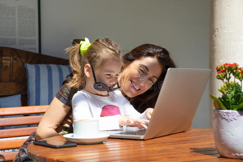 Funny little girl and mother laughing typing on laptop royalty free stock photography