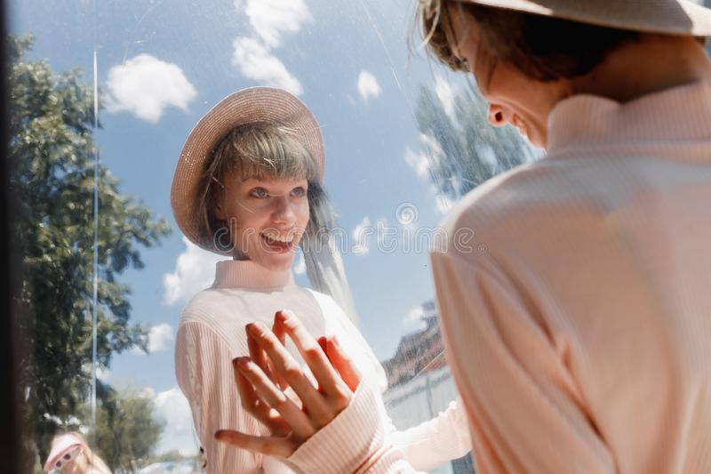 Funny girl in a gently pink dress and straw hat looks at her reflection in the mirror in the street on a sunny day royalty free stock images