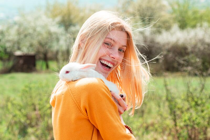 Funny girl hold rabbit on green field background. Closeup of winking girl with bunny rabbit. Lovely woman hold white royalty free stock images
