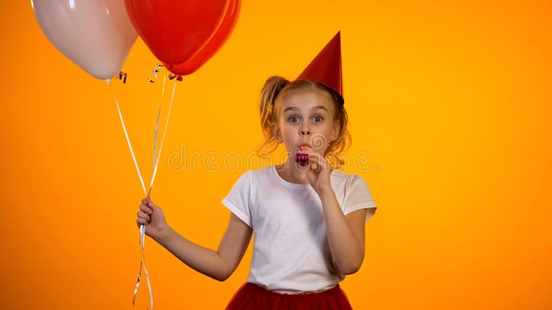 Funny girl holding air balloons and party blower celebrating birthday, happy stock photography