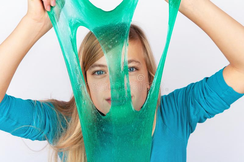 Funny girl holding a green slime and looking through its holes royalty free stock photos