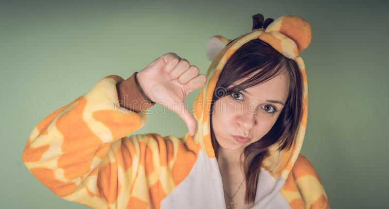 Funny girl in kigurumi pajamas. Emotional portrait of a student. costume presentation of children`s animator. Slippers in the form. Girl in a bright children`s royalty free stock photos