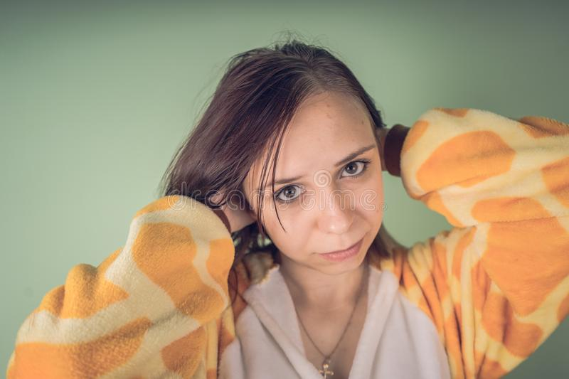 Funny girl in kigurumi pajamas. Emotional portrait of a student. costume presentation of children`s animator. Slippers in the form. Girl in a bright children`s royalty free stock photo