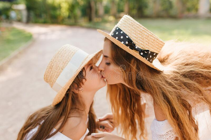 Funny girl with light-brown straight hair kissing mom during walk on the alley. Outdoor close-up portrait of lovely royalty free stock image