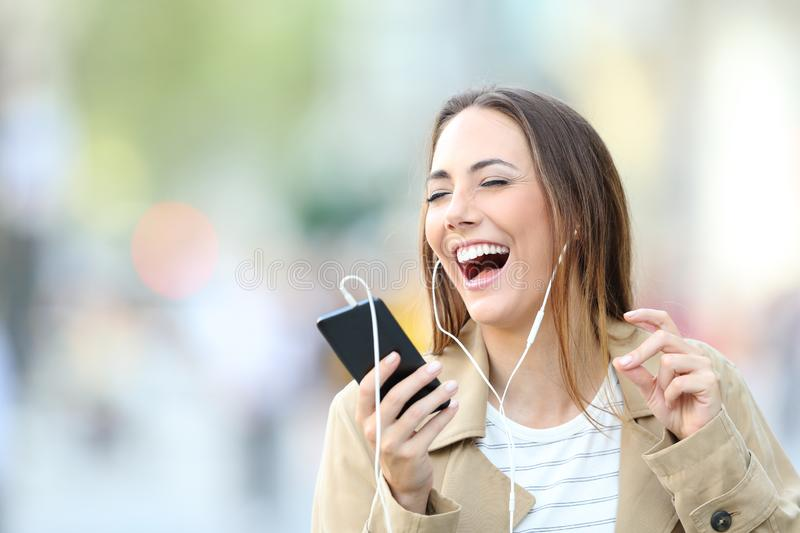 Funny girl listening to music and singing in the street stock image