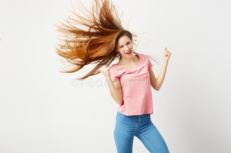 Funny girl with long hair fluttering in the wind dressed a pink t-shirt and jeans has fun on a white background in the royalty free stock images