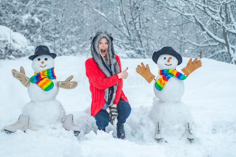 Funny Girl Love winter. Happy girl playing with a snowman on a snowy winter walk. royalty free stock photography